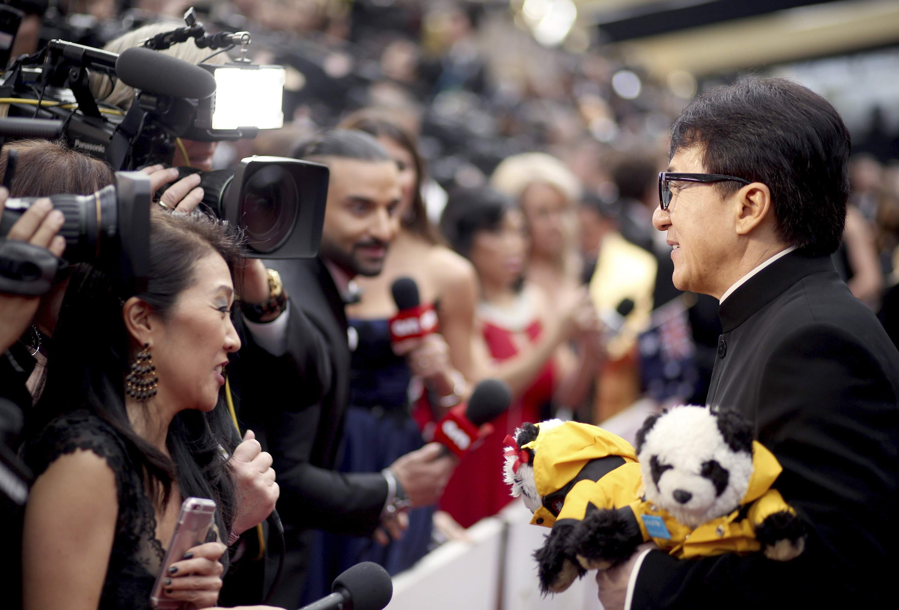 Jackie Chan greets the press at the Oscars on Sunday, Feb. 26, 2017, at the Dolby Theatre in Los Angeles. THE ASSOCIATED PRESS