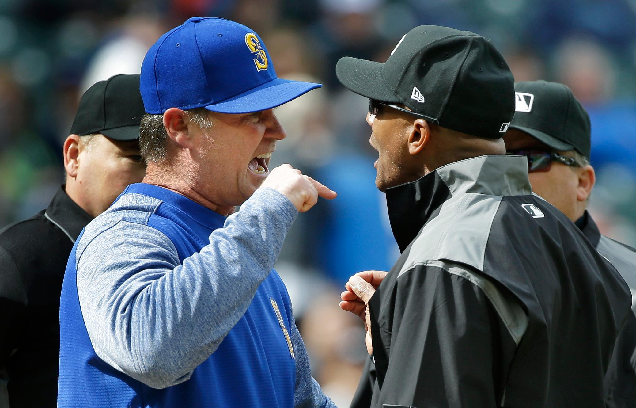Seattle Mariners manager Scott Servais, left, argues with first base umpire CB Bucknor, right, before being ejected from the game during the sixth inning of a baseball game against the Texas Rangers, Sunday, April 16, 2017, in Seattle. Servais was arguing about a ball hit near the first base foul line by Mariners' Leonys Martin. (AP Photo/Ted S. Warren)