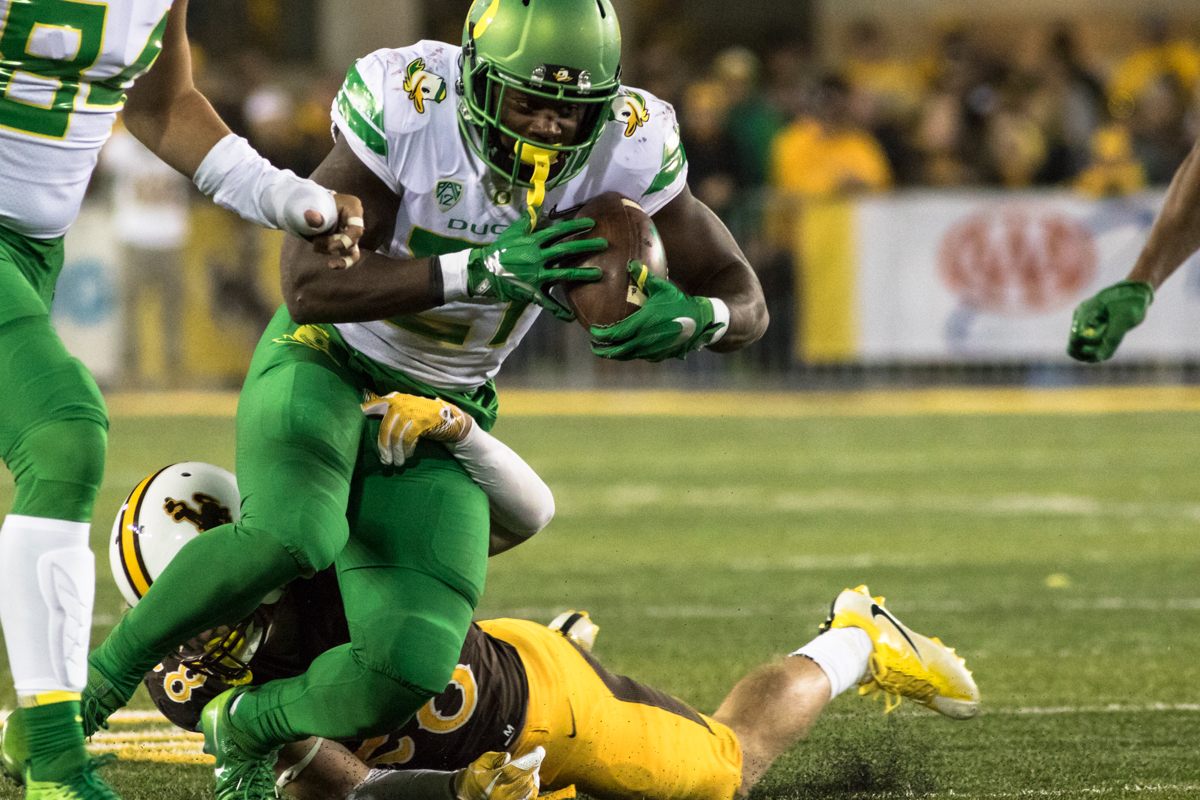 Oregon running back Royce Freeman (#21) tries to shake Wyoming safety Andrew Wingard (#28). The Oregon Ducks recorded their first road win under head coach Willie Taggart with their 49-13 victory over the Wyoming Cowboys on a cold night at War Memorial Stadium in Laramie, Wyoming.  Photo by Austin Hicks, Oregon News Lab