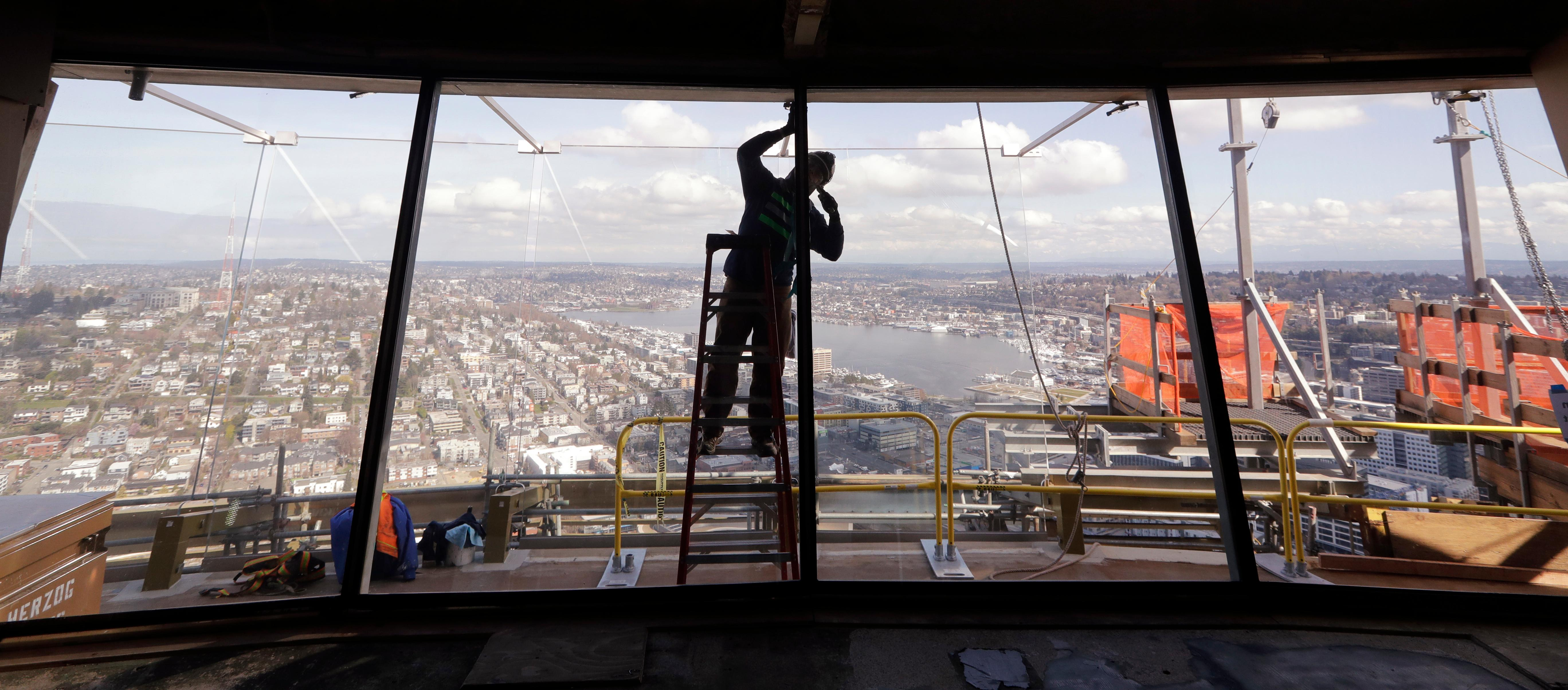 FILE - In this March 20, 2018, file photo, a glazer works on glass panels on the exterior wall of the Space Needle observation deck where larger glass panels behind him begin to line the exterior viewing platform and views north in Seattle. The privately-funded, $100 million renovation of the 55-year old structure is designed to increase the views 500-some feet above ground. It will include the replacement of wire barriers on the observation deck with outward-slanted glass and short exterior walls will be replaced with the floor-to-ceiling glass panels. (AP Photo/Elaine Thompson)