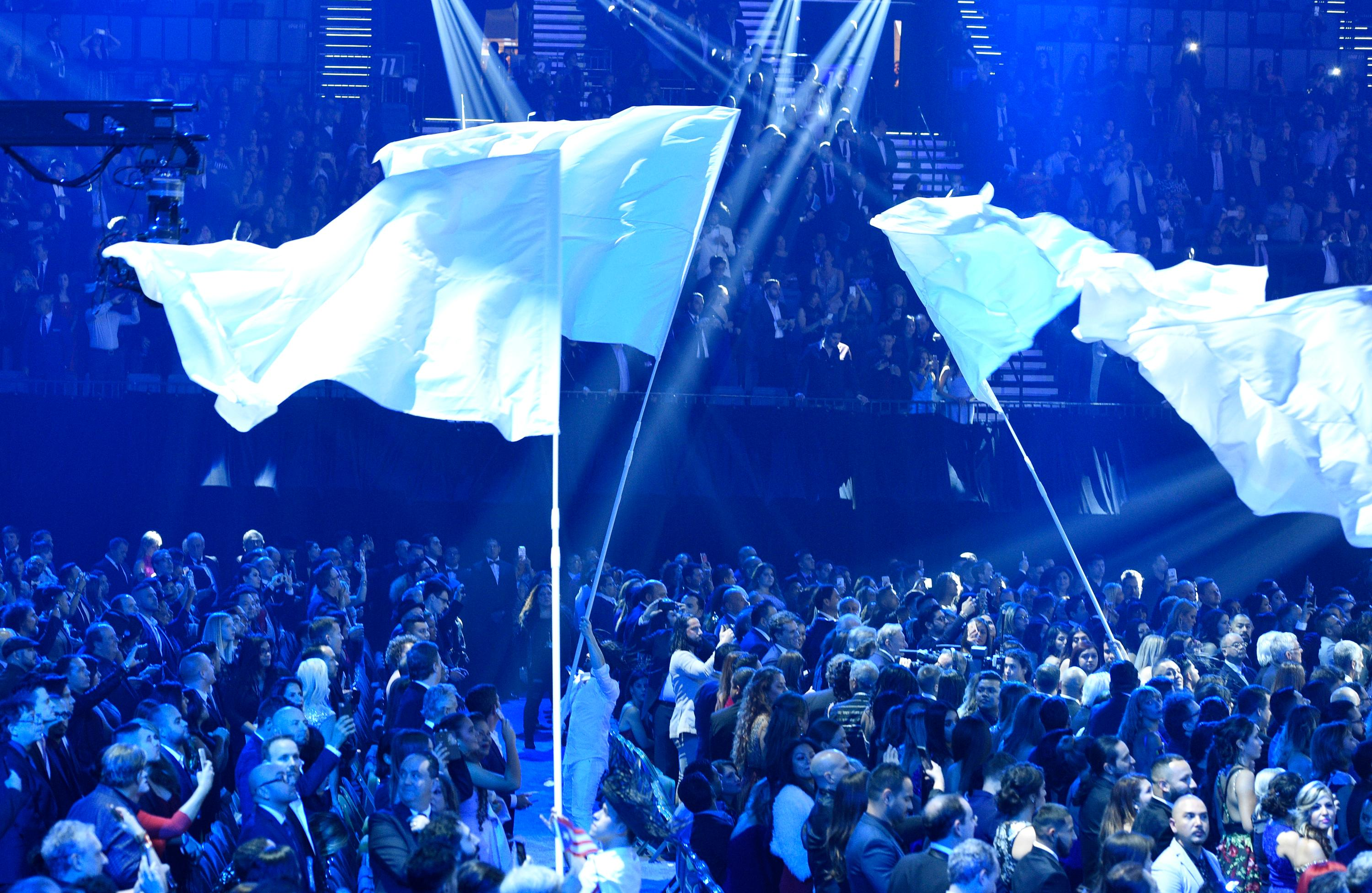 "Performers wave flags as Residente performs ""Hijos del Canaveral"" at the 18th annual Latin Grammy Awards at the MGM Grand Garden Arena on Thursday, Nov. 16, 2017, in Las Vegas. (Photo by Chris Pizzello/Invision/AP)"