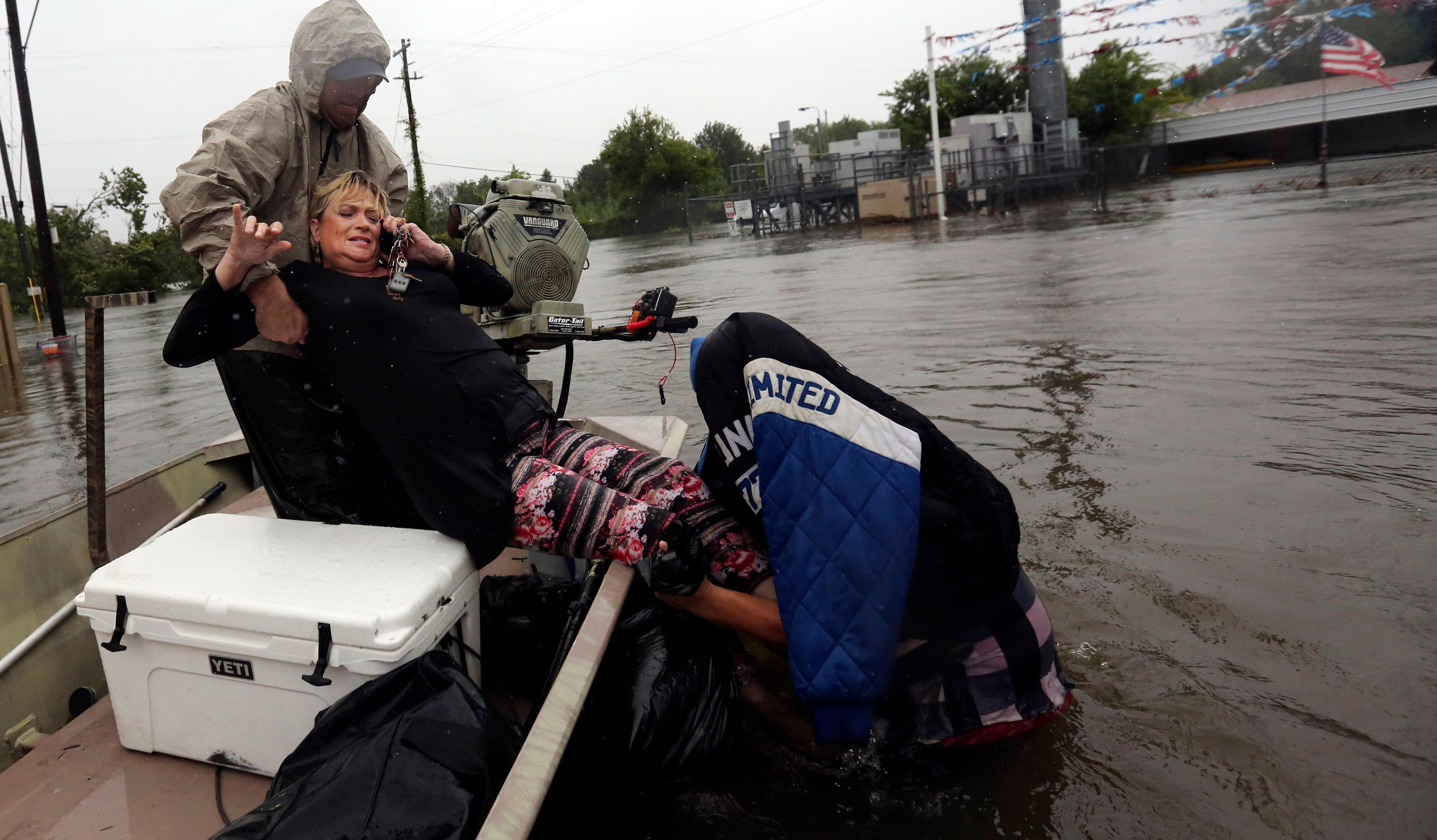 Rhonda Worthington is lifted into a boat while on her cellphone with a 911 dispatcher after her car became stuck in rising floodwaters from Tropical Storm Harvey in Houston, Texas, Monday, Aug. 28, 2017. (AP Photo/LM Otero)