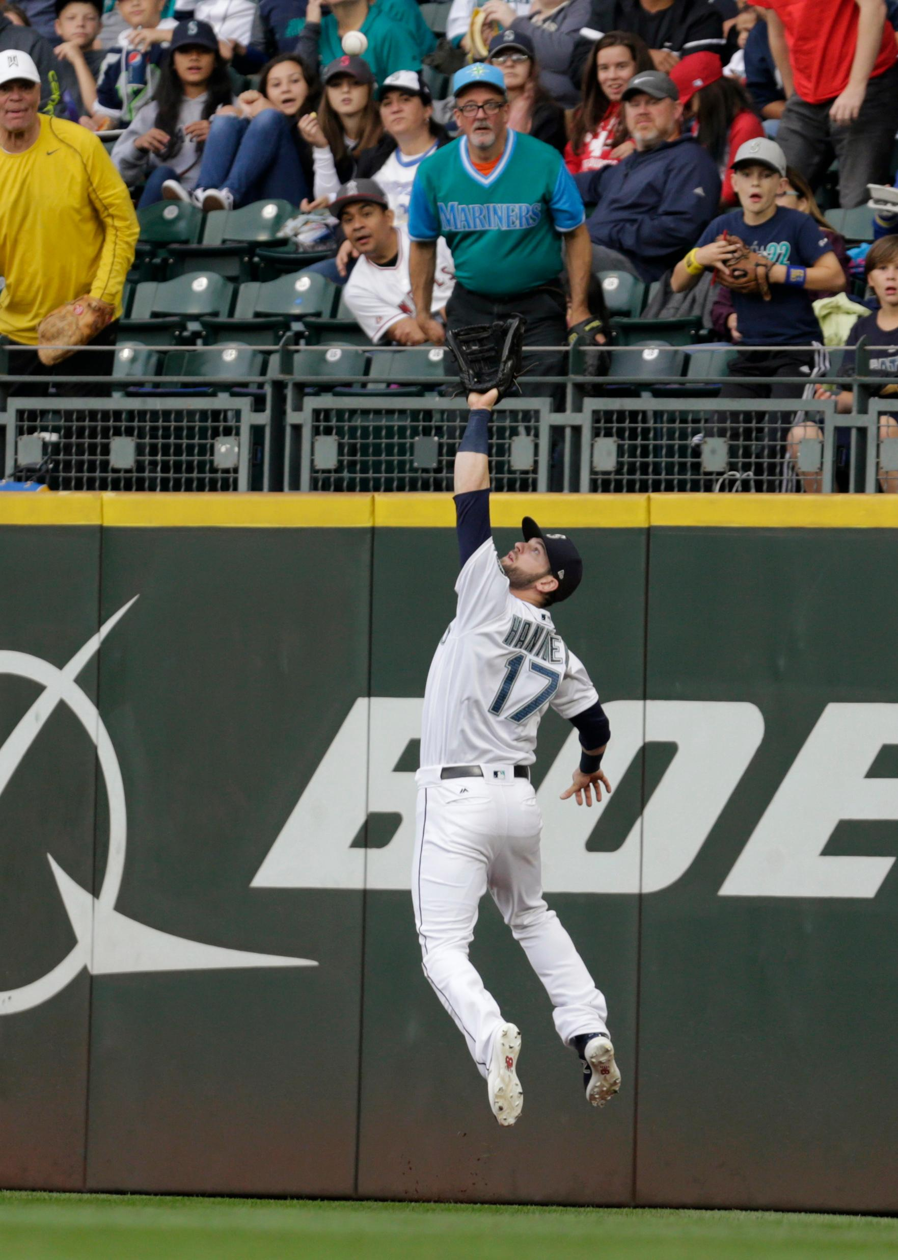 Seattle Mariners right fielder Mitch Haniger leaps to catch a fly ball for the out on Los Angeles Angels' Justin Upton during the first inning of a baseball game Saturday, Sept. 9, 2017, in Seattle. (AP Photo/John Froschauer)