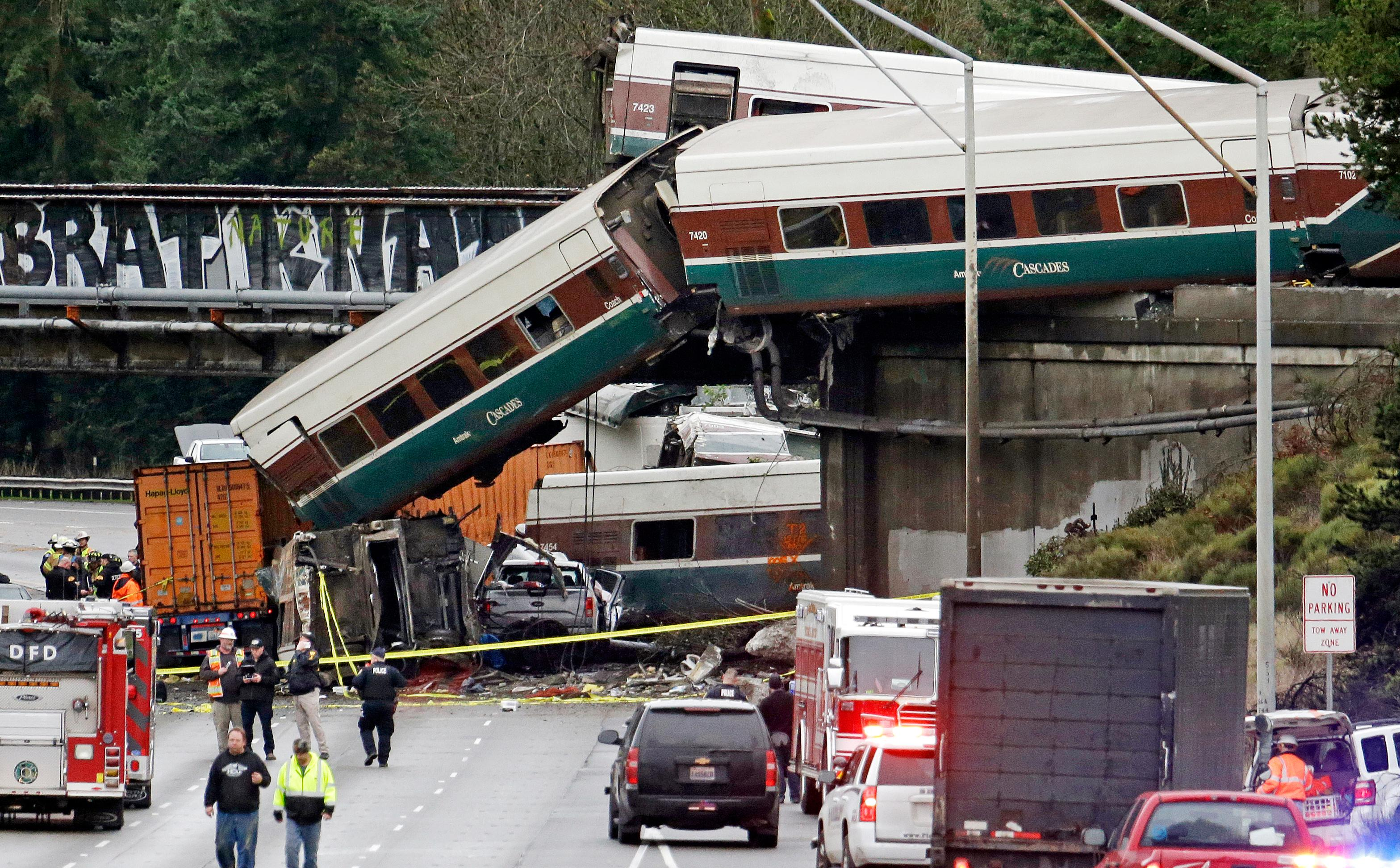 Cars from an Amtrak train lay spilled onto Interstate 5 below alongside smashed vehicles as some train cars remain on the tracks above Monday, Dec. 18, 2017, in DuPont, Wash. The Amtrak train making the first-ever run along a faster new route hurtled off the overpass Monday near Tacoma and spilled some of its cars onto the highway below, killing some people, authorities said. Seventy-eight passengers and five crew members were aboard when the train moving at more than 80 mph derailed about 40 miles south of Seattle before 8 a.m., Amtrak said. (AP Photo/Elaine Thompson)