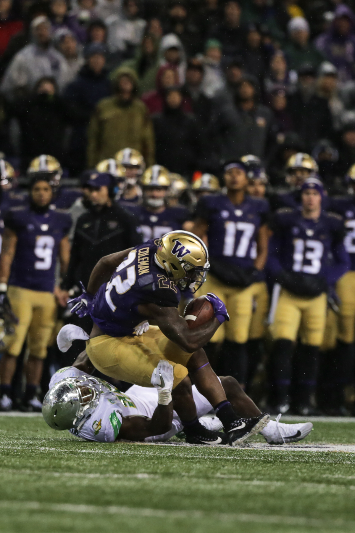 Washington running back Lavon Coleman (#22) is dragged down by Oregon linebacker Jimmie Swain (#18). The Oregon Ducks fell to the Washington Huskies 38 - 3 on a cold and rainy night in Seattle, Washington.  Oregon opened the game with a field goal on their first drive and was held scoreless from then on.  Photo by Austin Hicks, Oregon News Lab