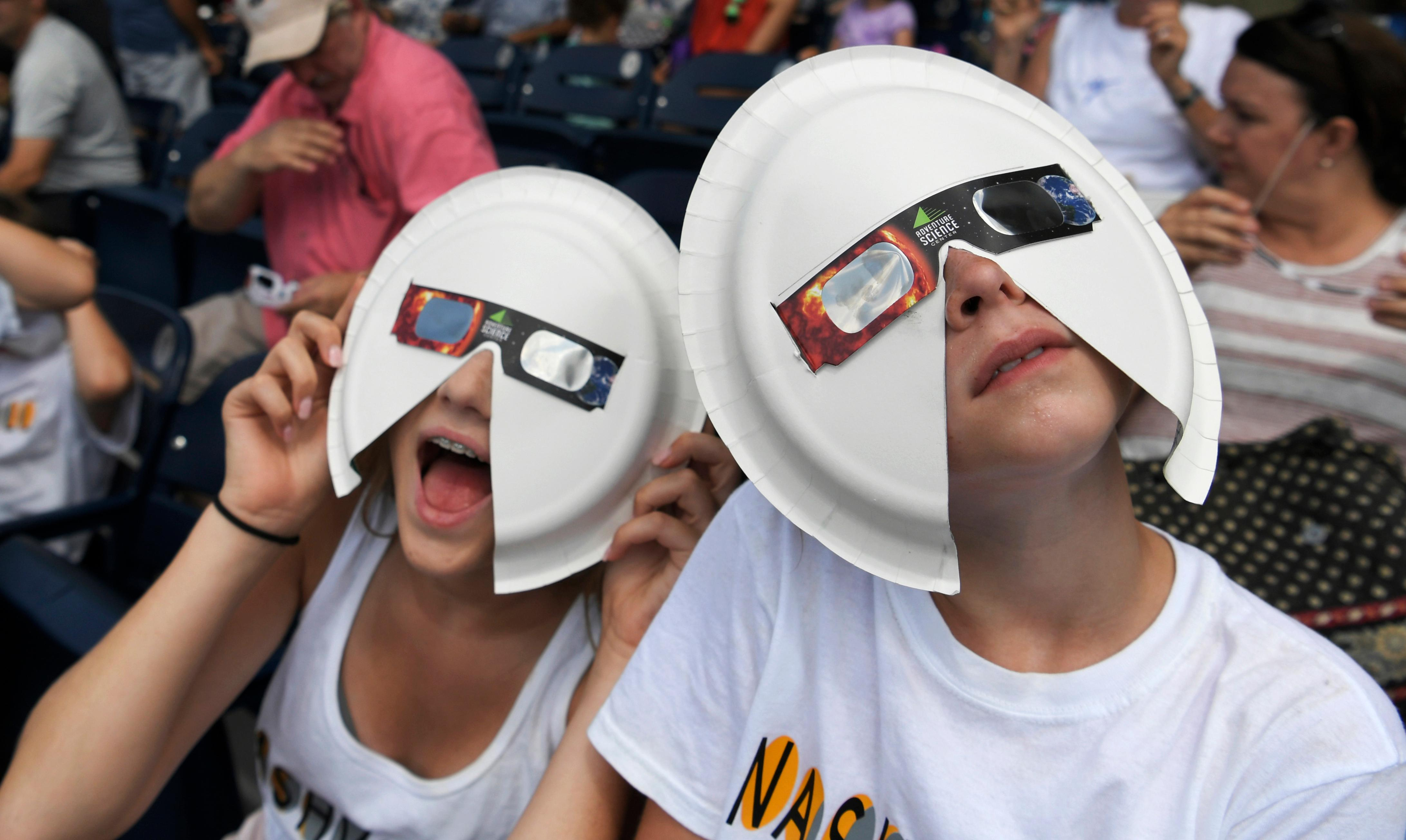Annie Gray Penuel and Lauren Peck, both of Dallas, wear their makeshift eclipse glasses at Nashville's eclipse viewing party ahead of the solar eclipse at First Tennessee Park on Monday, Aug. 21, 2017, in Nashville, Tenn. (Shelley Mays/The Tennessean via AP)