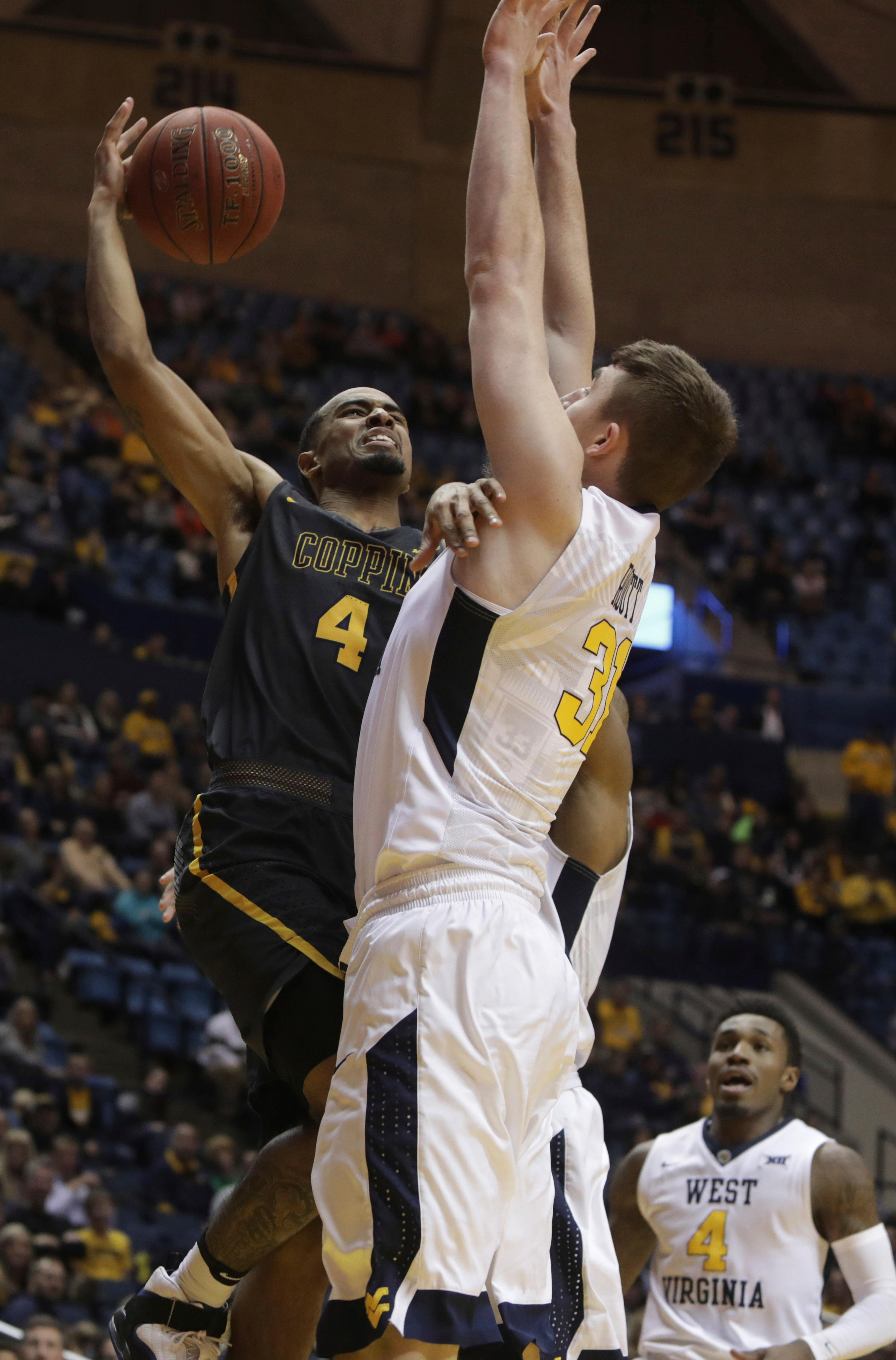 Coppin State guard Tre' Thomas (4) drives to the basket as West Virginia forward Logan Routt (31) defends during the first half of an NCAA college basketball game Wednesday, Dec. 20, 2017, in Morgantown, W.Va. (AP Photo/Raymond Thompson)