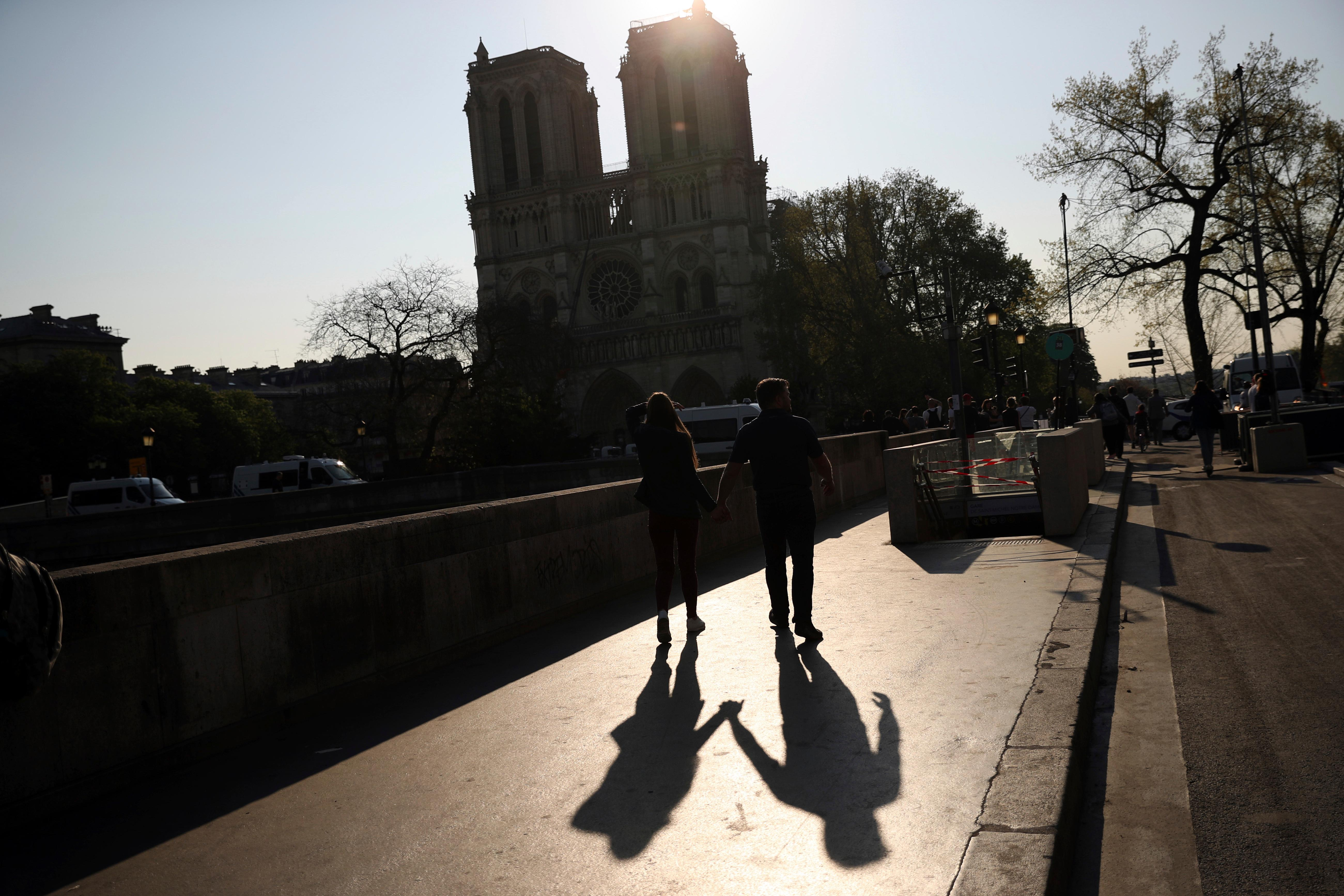 Two people walk by a the Notre Dame Cathedral in Paris, Saturday, April 20, 2019. Yellow vest protests are scheduled to take place in Paris and other regions of France over the weekend, with a heightened security presence anticipated. (AP Photo/Francisco Seco)