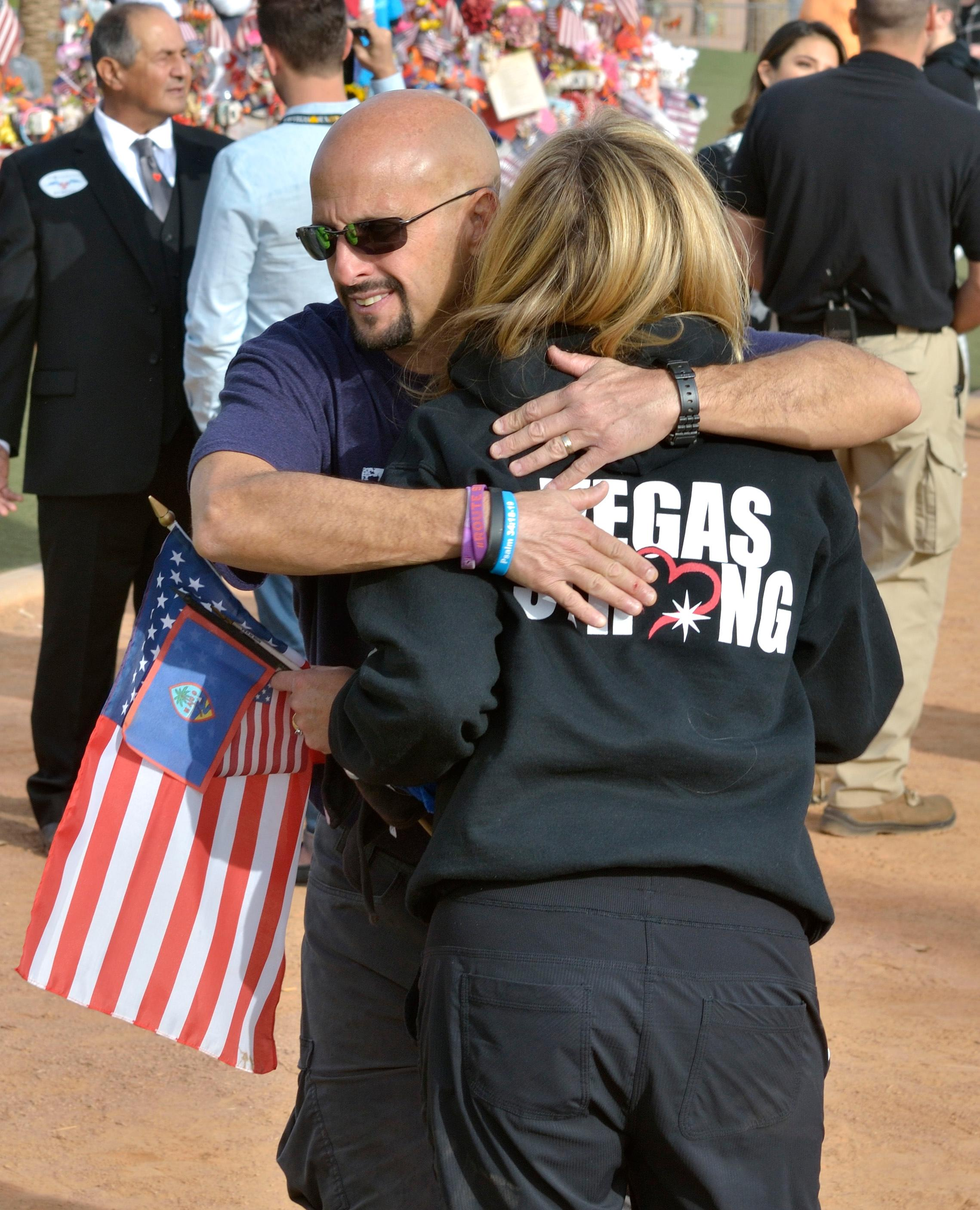 "Mynda Smith gets a hug from Rich Purdy, youth pastor at Calvary Lane Mountain Church, near a memorial cross for her sister Neysa Tonks during ""Greg Zanis Day"" at the Welcome to Fabulous Las Vegas sign on the Las Vegas Strip on Sunday, Nov. 12, 2017. Zanis, a carpenter from Aurora, Ill., was recognized by the Clark County Commision for creating 58 crosses memorializing those who died during the Route 91 Harvest festival shooting on Oct. 1. The crosses were later moved to the Clark County Museum for its permanent collection. [Bill Hughes/Las Vegas News Bureau]"
