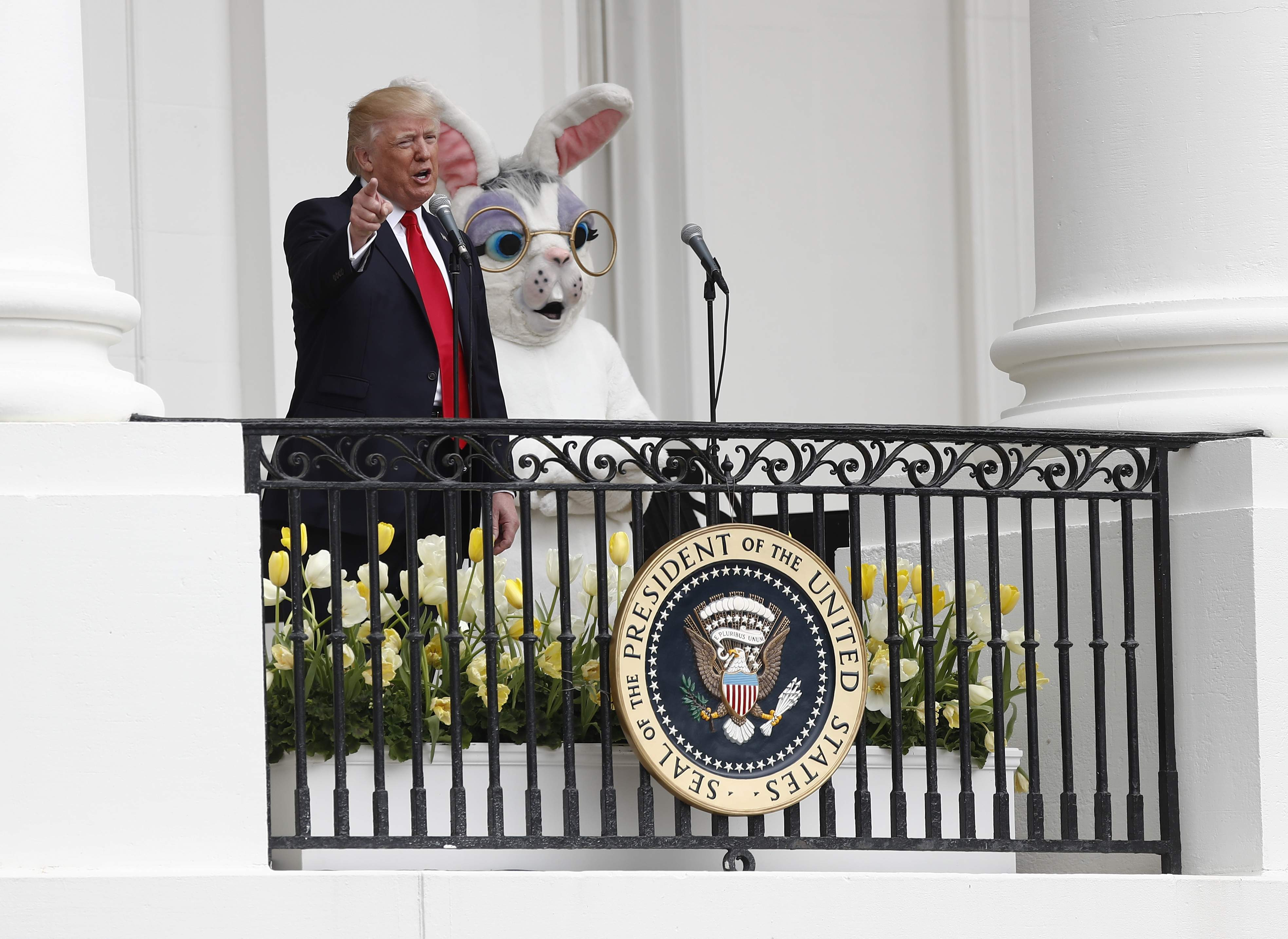 DAY 88 - In this April 17, 2017, file photo, President Donald Trump, joined by the Easter Bunny, speaks from the Truman Balcony during the annual White House Easter Egg Roll on the South Lawn of the White House in Washington. (AP Photo/Carolyn Kaster, File)