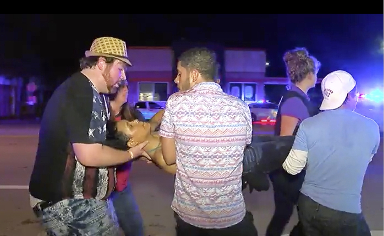 An injured person is escorted out of the Pulse nightclub after a shooting rampage, Sunday morning June 12, 2016, in Orlando, Fla.  (AP Photo/Steven Fernandez)