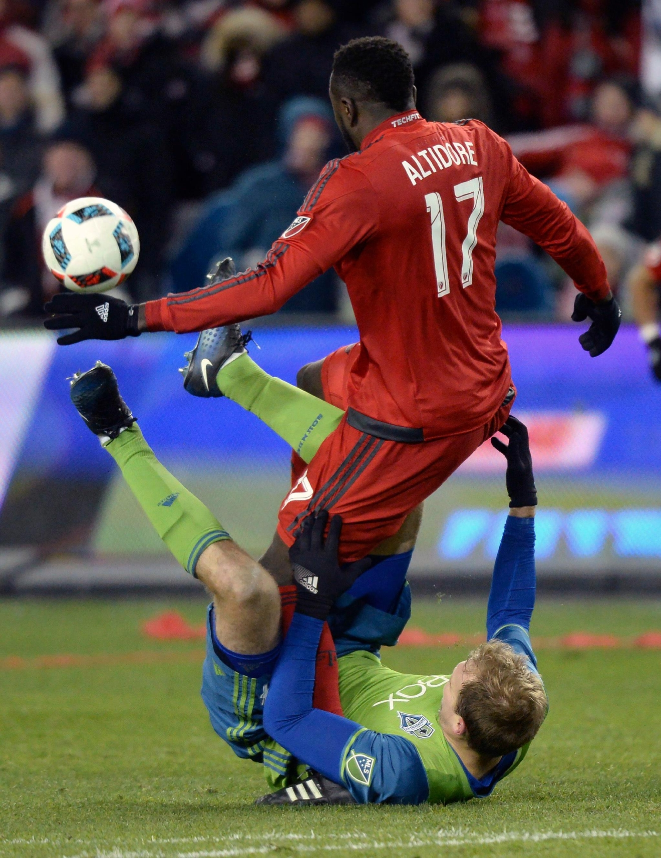 Seattle Sounders defender Chad Marshall, bottom, is taken down by Toronto FC forward Jozy Altidore (17) during second-half MLS Cup final soccer action in Toronto, Saturday, Dec. 10, 2016. (Nathan Denette/The Canadian Press via AP)